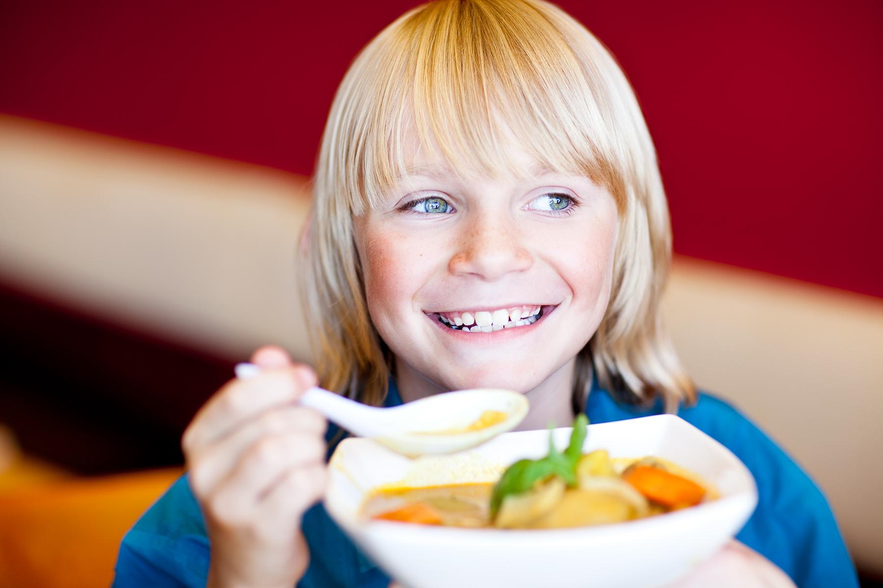 smiling blonde boy eating kids art director photography